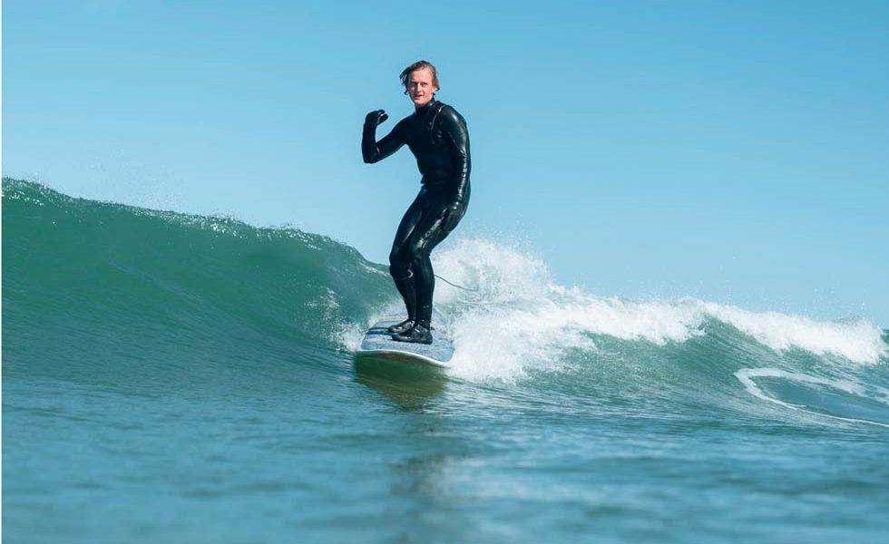 Mand surfer på bølgerne i Løkken - kultur i Hjørring i naturen